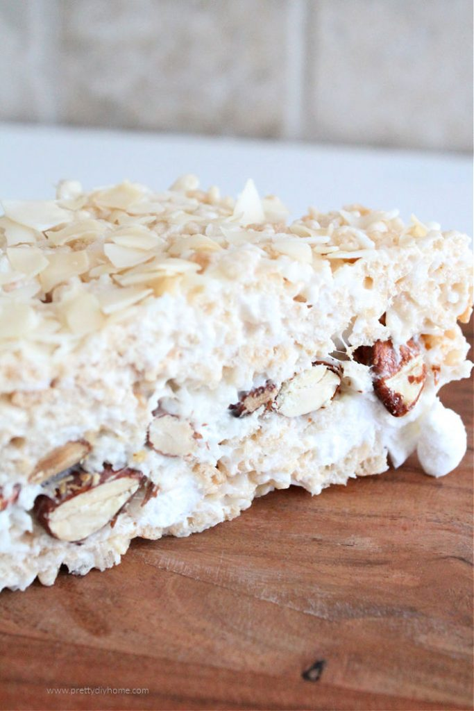 No bake squares with layers of rice krispies and a thick layer of marshmallow almonds and coconut in the middle