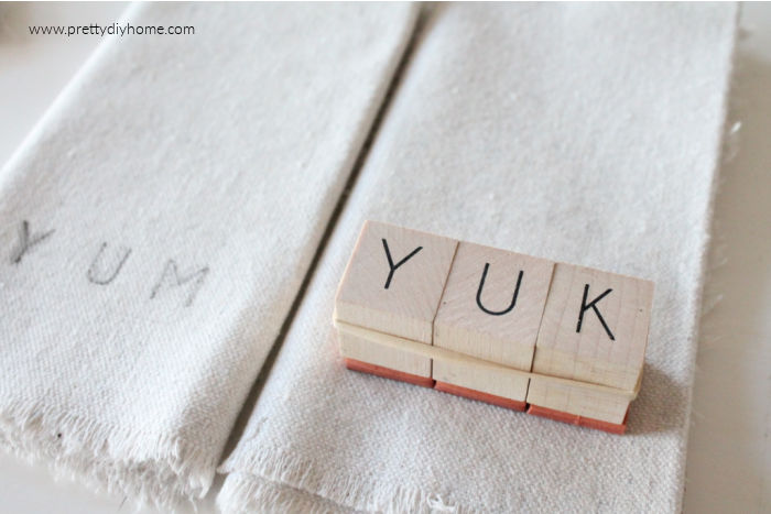 YUK spelled out on with wood stamps. The stamp is bundled together with elastic and is making a DIY stamped fabric napkin craft.