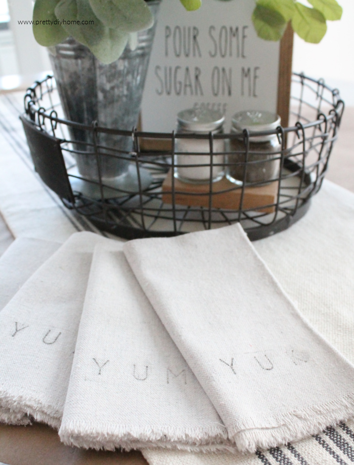 Hand made no sew fabric napkins with fringe edging, stamped with the words Yuk and Yum. The napkins are part of a farmhouse kitchen table setting.
