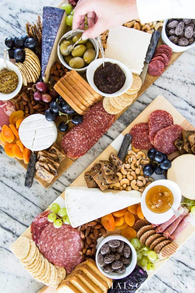 Large dark antique looking charcuterie boards covered with fruit, cheese and sausage.