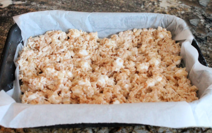 The first layer of layered rice krispie square recipe.
