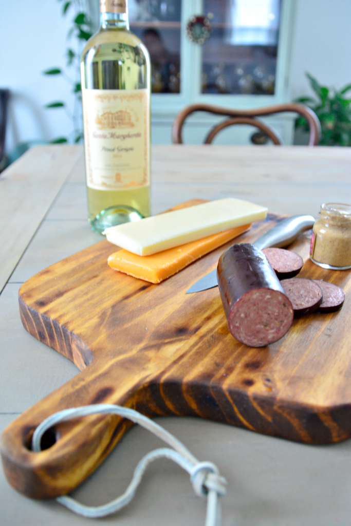 A large handmade charcuterie board stained dark with coffee. This DIY charcuterie board had a handle and is serving meat and cheese with a bottle of wine in the background.