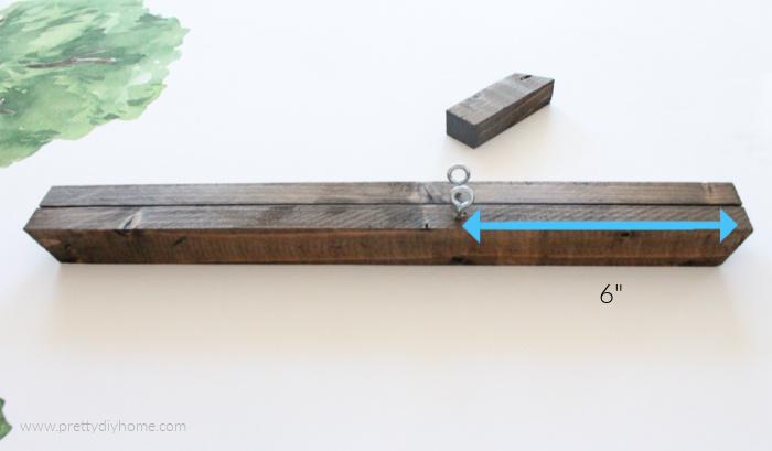 Placing screw eyes into a wooden poster frame, showing six inches from the end.