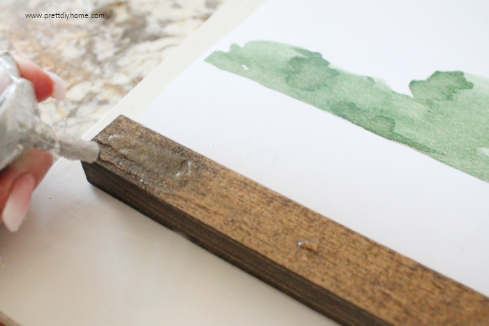 Adding glue to the back side of a wooden frame for making DIY farmhouse wall decor.
