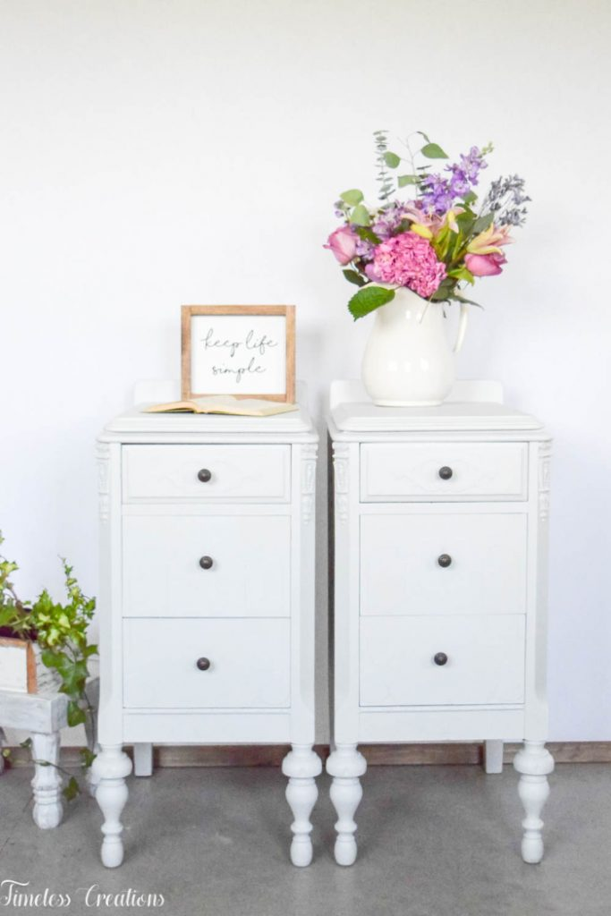 An antique side table upcycle into two white nightstands. The tall night stands have three drawers each, its finished in matte white paint, and there is a white pitcher full of bright flowers on top.