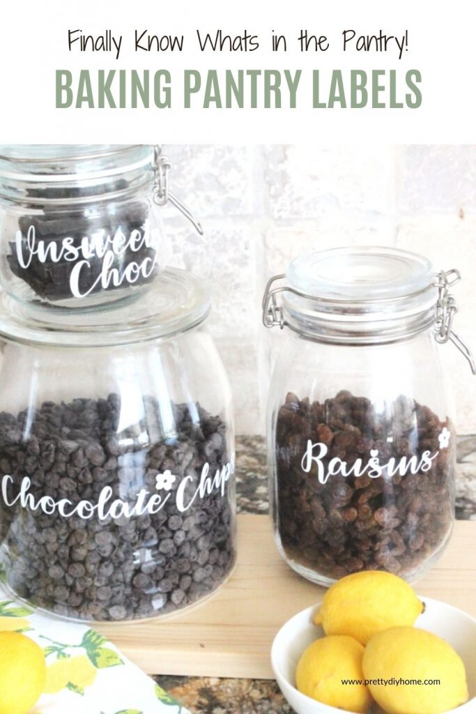 Three IKEA jars in different sizes sitting on a counter with a light cutting board, and lemons. The jars have white modern farmhouse style DIY baking pantry labels that say chocolate chips, raisins, and unsweetened chocolate.