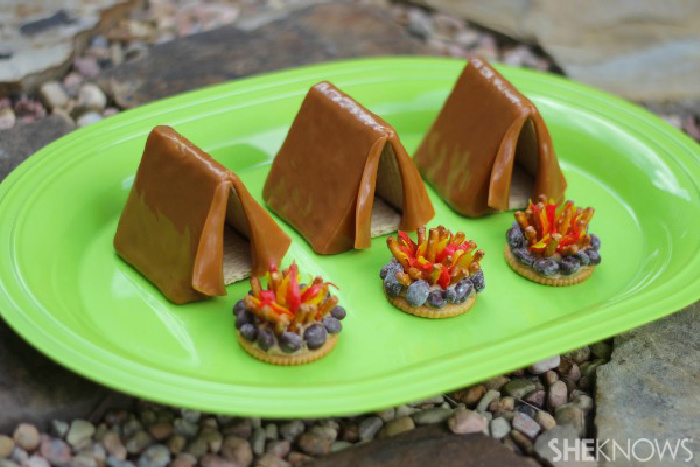 Three mini tent made out of caramel with three tiny fire made out of cookies and chocolate chips