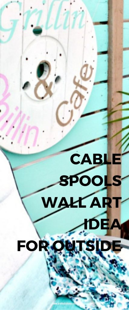 A large cable spool upcycled into a DIY Grillin and Chillin Patio Sign. The sign is hung on a turquoise privacy screen, and the Grillin and Chillin test is in bright pink, turquoise and gold lettering.