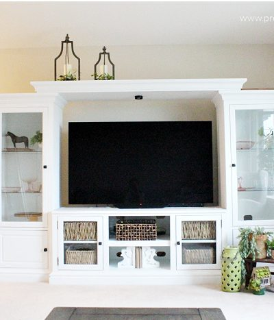 Fixed and painted white DIY Entertainment center makeover, in white with storage baskets.`