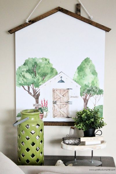 A poster hanger with watercolour farmhouse printable scene. The frame is brown and looks like a cottage roof.