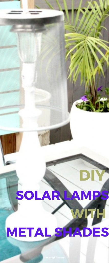 An upcyled solar lamp sitting on a patio table. The lamp is painted white and it has a metal lamp shade made from a dollar store waste paper basket.