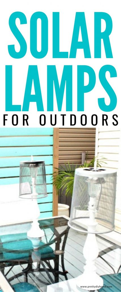 two DIY solar light lanterns made from upcycled lamps, with metal shades sitting out on a clear glass table.