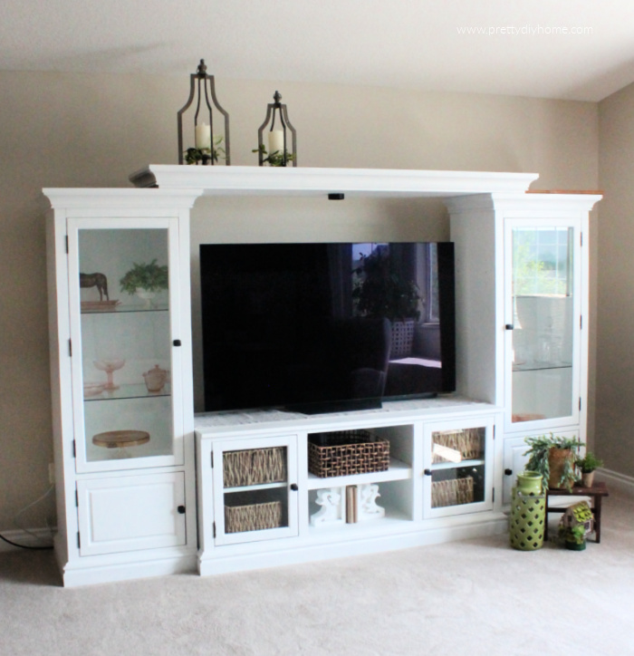 A painted entertainment center after picture. Its white with greenery and pink depression glass, and wicker baskets.