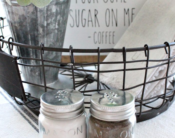 A farmhouse kitchen basket centerpiece in neutral colours with a set of mason jar diy salt and pepper shakers in front.