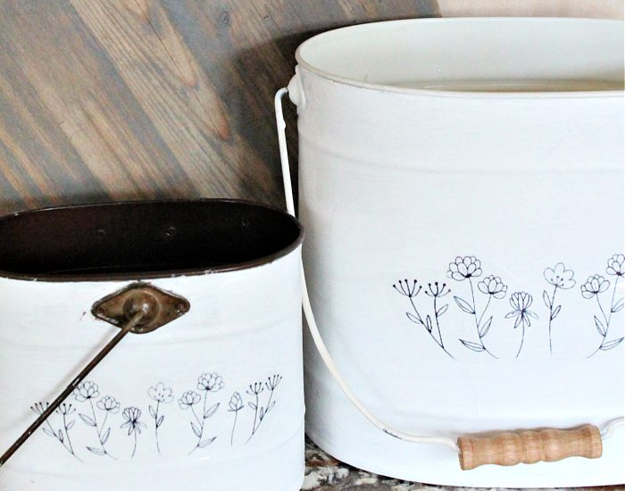 Two farmhouse DIY bucket makeovers in white with black flowers sketches on the front.