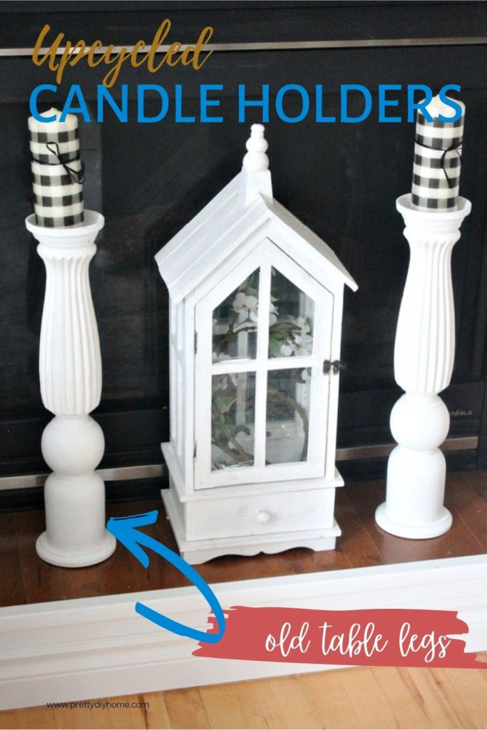 A farmhouse style fireplace mantel with a white lantern paired with two large wooden candlesticks in white paint.
