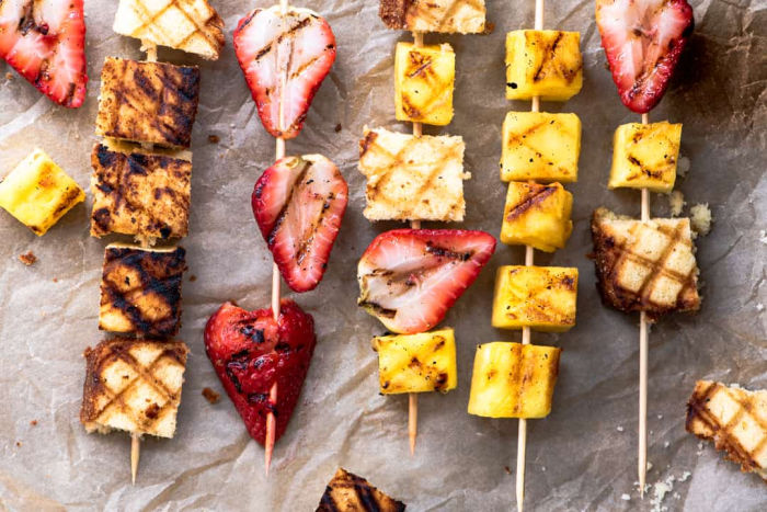 An easy camping dessert recipe, grilled shortcake skewers with shortcake bits, fresh pineapple and strawberries layed out onto skewers.