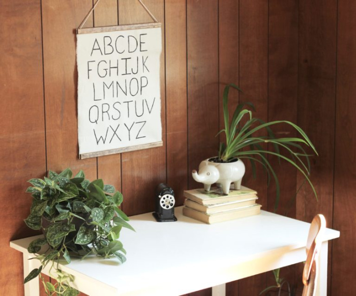 A handmade poster hanging over a desk that has plants a