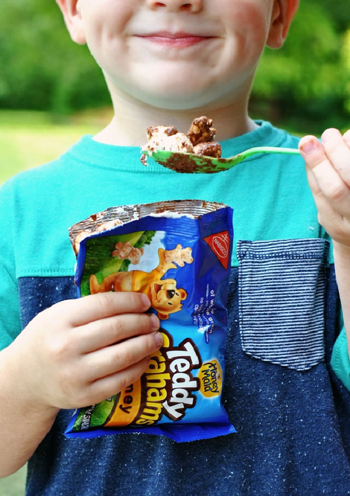 A little boy with a big smile holding a bag full of less mess s'mores recipe.