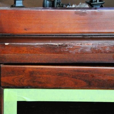 The Before picture of lifted veneer on a entertainment center