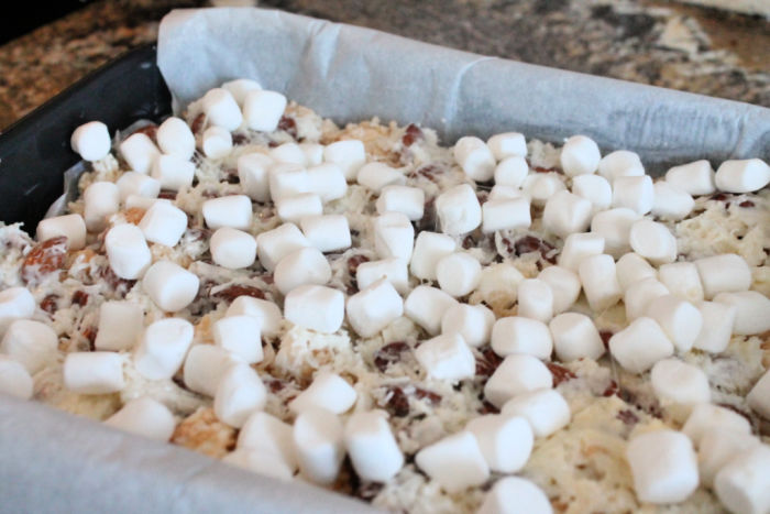 Miniature marshmallows scattered on a layer of coconut and almonds.