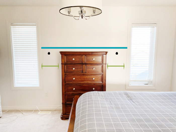 Measuring the placement of diy peg rail shelving in a bedroom around a dresser.