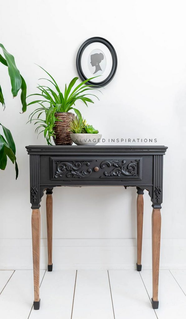 A striking dramatic furniture upcycle on an old sewing stand with legs. The top is black paint and the bottom of the long legs. The actual legs of this table are in a bare wood.