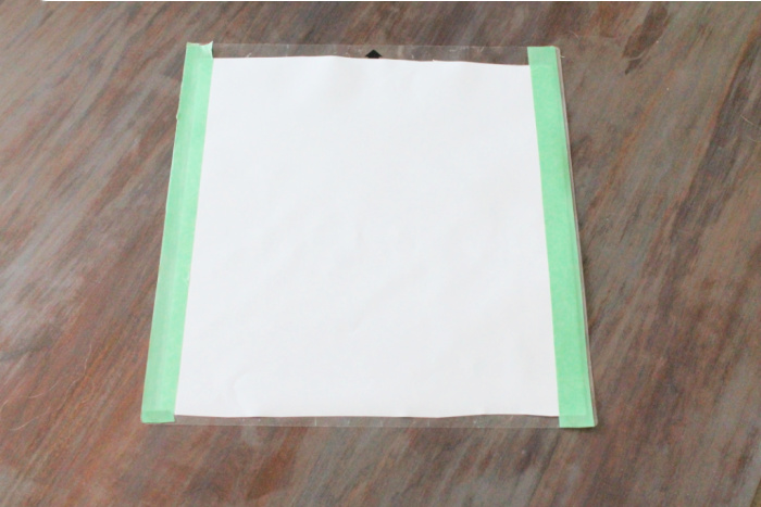 A Silhouette cutting mat with white vinyl showing how the edges are taped down with green tape to make the rollers hold in place while cutting.