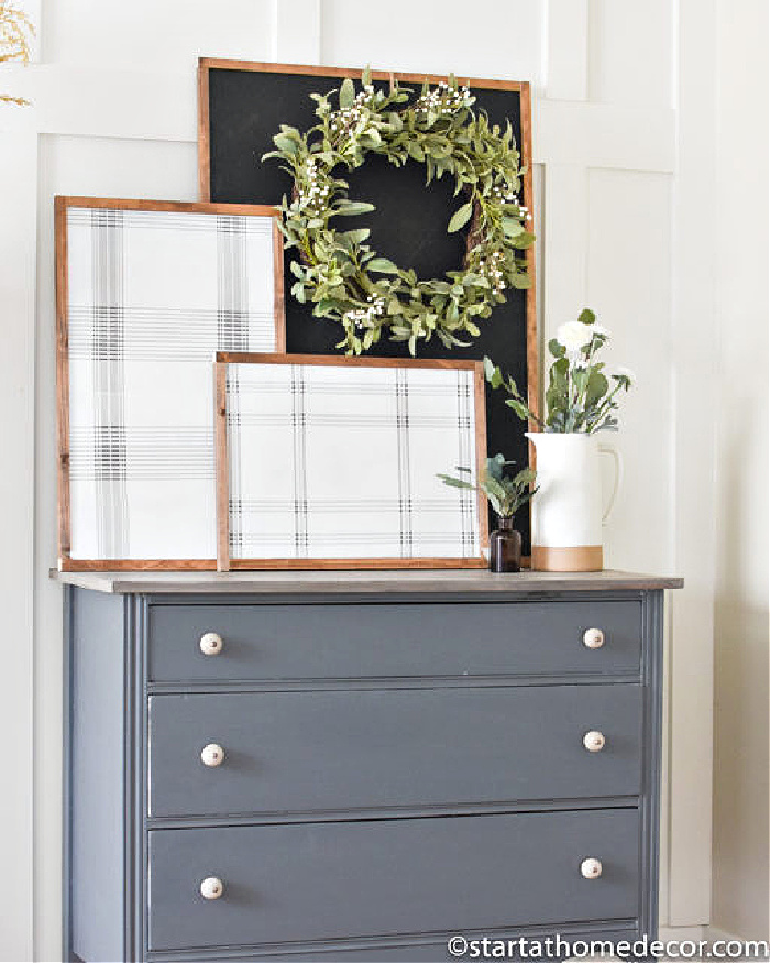 Two DIY plaid art frames with wood frames, and a chalkboard background. The artwork is arranged on top of a grey dresser.