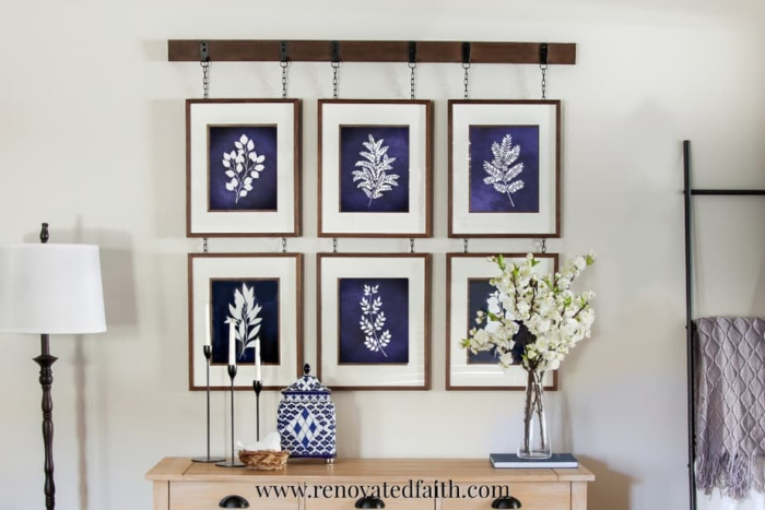 A hanging rail rack diy wall art idea. A wood strip is attached to the wall and then a collection of six different blue botanical prints hanging from it in frames.