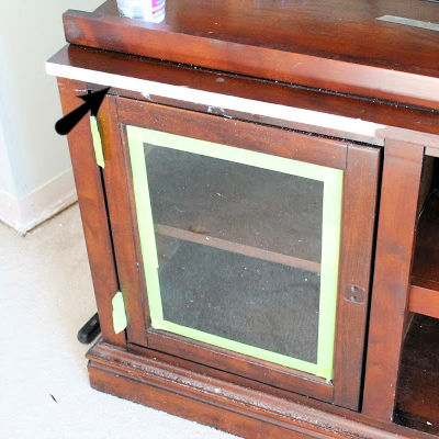 Repair of damaged laminate on an entertainment center.