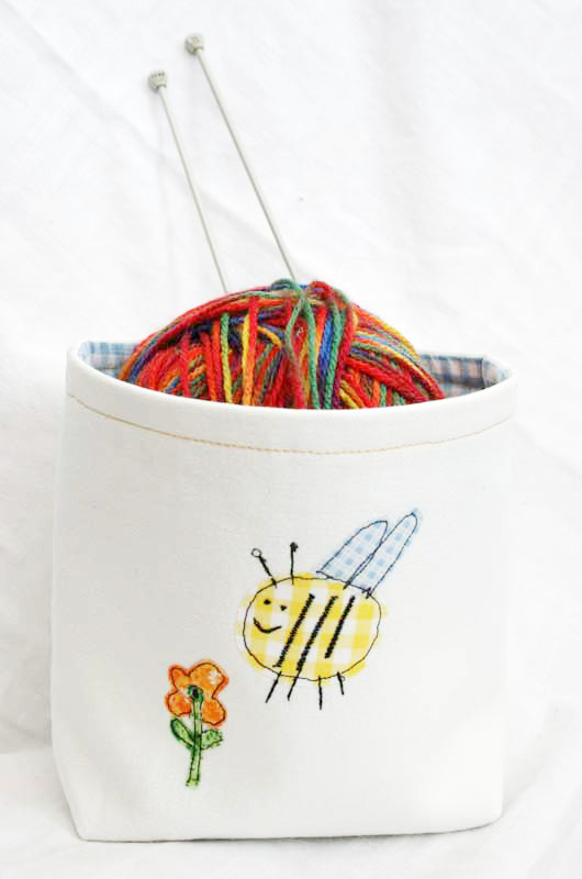 A sewn DIY fabric basket in cream with a fun bumblebee applique on the front. The DIY fabric bin has a ball of yarn inside with two knitting needles.