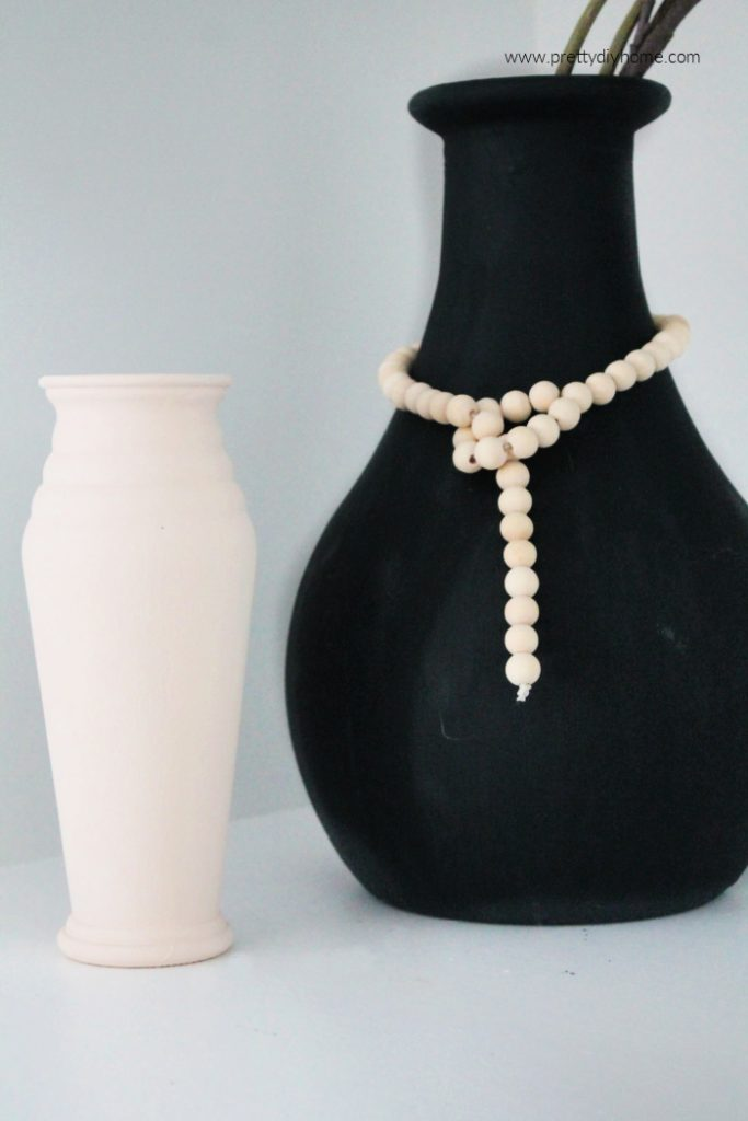 A large black faux ceramic diy vase in black with a wooden string of farmhouse beads with a loop hanging around the vase.  There is a small diy faux ceramic cream vase sitting beside it.