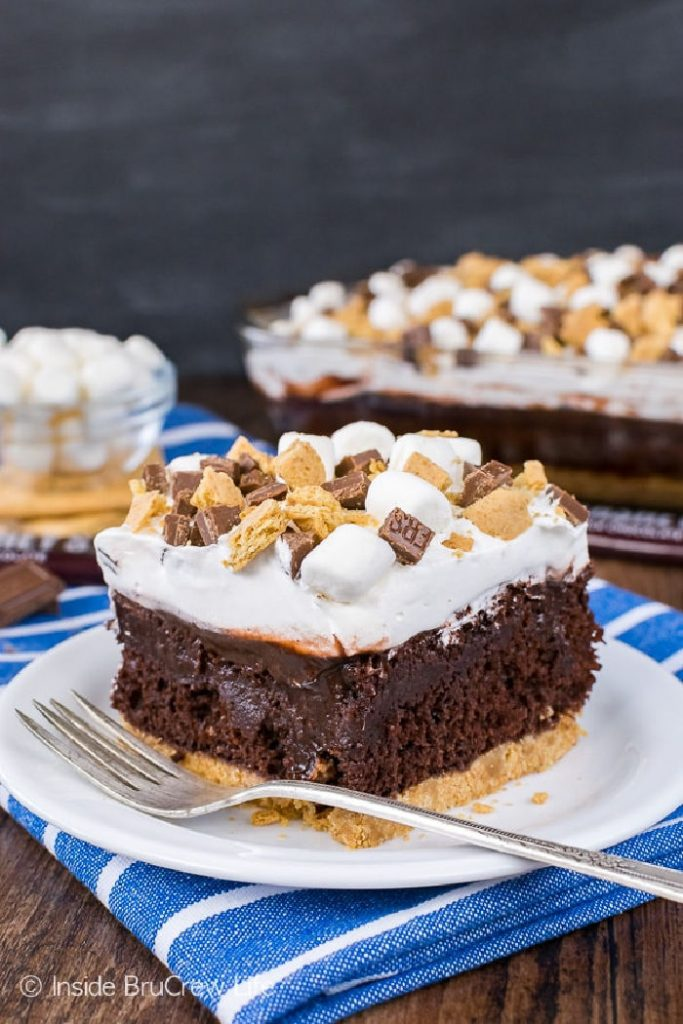 A large centered piece of chocolate Smores pudding cake with layers of graham crust, chocolate putddimg, melted marshmallows and crunchy bits of graham cookies, mini marshmallows and chocolate bits.