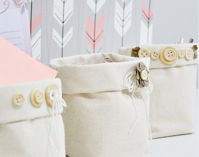 Three DIY fabric storage bin baskets you can make for free. The fabric baskets are sewn using canvas duck cloth, and have a farmhouse stylee with simple button flowers as embellishments. There are three little fabric baskets one is holding a notepad, the middle one is holding pens, and the third one is holding
