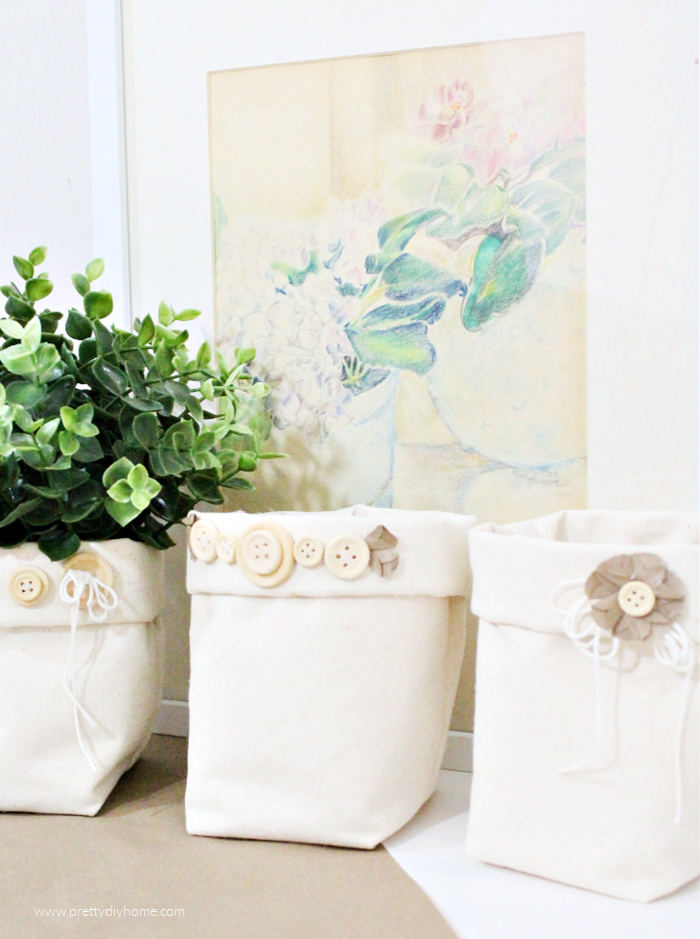 Three DIY fabric storage bins for the home office. The bins are cream cotton with pretty farmhouse button embellishments, there is a soft floral watercolour in a frame behind them.