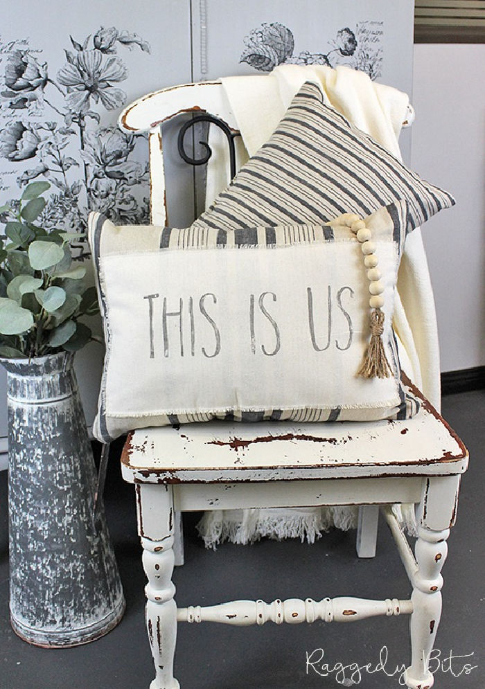A DIY Farmhouse stamped tea towel that says THIS IS US, made into a oblong shaped cushion with grey striped fabric. The cushion is sitting on a white chippy painted chair, with a second cushion and a cream coloured throw behnd it.