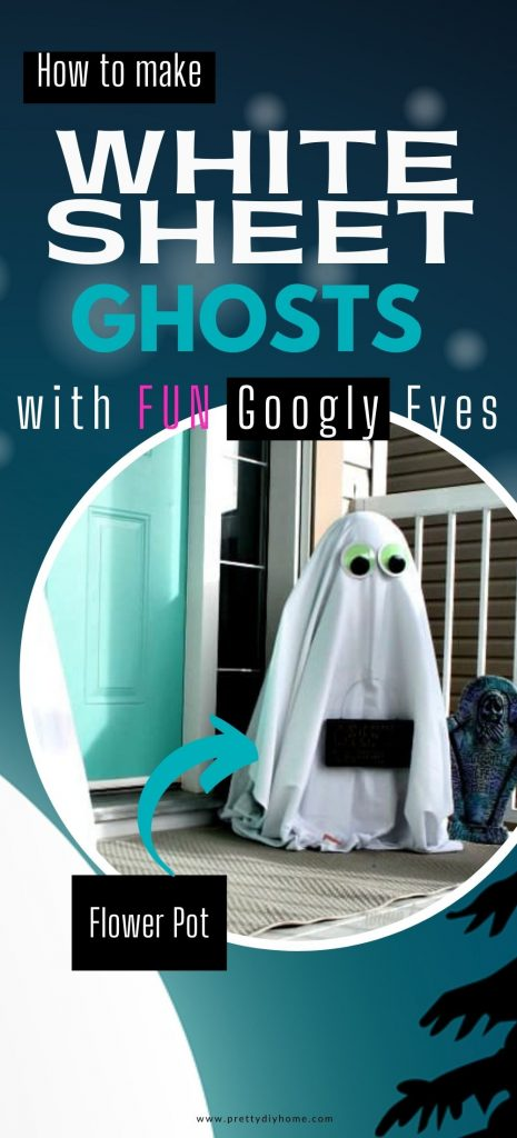 A DIY Halloween ghost made with a white sheet and flower pots. He has a sad face from holding a sign that says Happy Halloween. The white sheet porch ghost is about 3 feet tall and there are two of them sitting on each side of the front door.