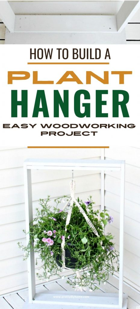 A large DIY hanging plant stand built out of scrap wood. It is painted white and it holding a large flowered plant. The plant hanger is sitting on the front porch beside the front door.