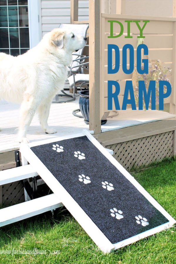 The back yard deck of a house with a large GreatPyrenees standing at the top of a handmade DIY dog ramp, The DIY dog ramp is white with a black outdoor rug, stamped with large white doggie prints.
