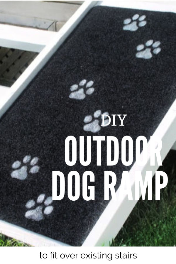 A large DIY dog ramp sitting in a back yard over the back deck stairs. The dog ramp is made out of lumber, with white paint, and it has a black outdoor rug for traction with hand painted large dog paw prints on it.