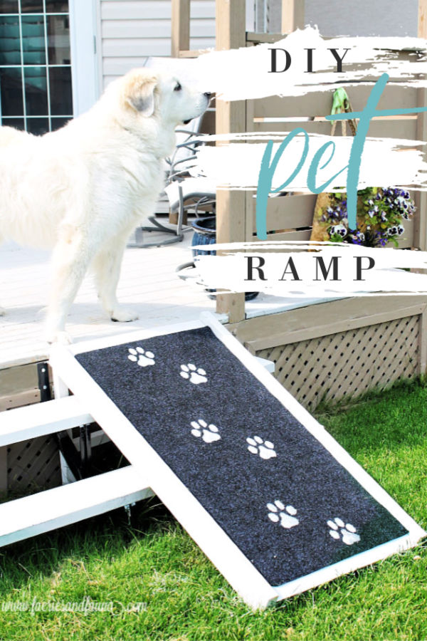 A giant Great Pyrenees standing at the top of a DIY pet ramp, The DIY dog ramp isbuild using wood, has white paint a black outdoor rug for traction and is stamped with large white doggie prints.