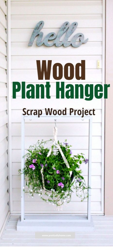 A large diy planter hanger sitting outdoor on the front porch. The plant hanger is made out of wood, painted white and has a large flower pot of petunias and vines hanging from it.