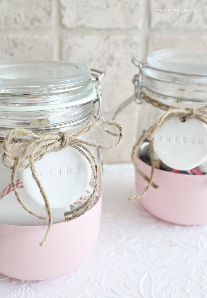 A DIY glass jar makeover starting with plain IKEA jars, that are painted, and tagged with DIY polymer clay labels, that are attached using twine. There are two jars, one holding washi tape, the other is filled with buttons.