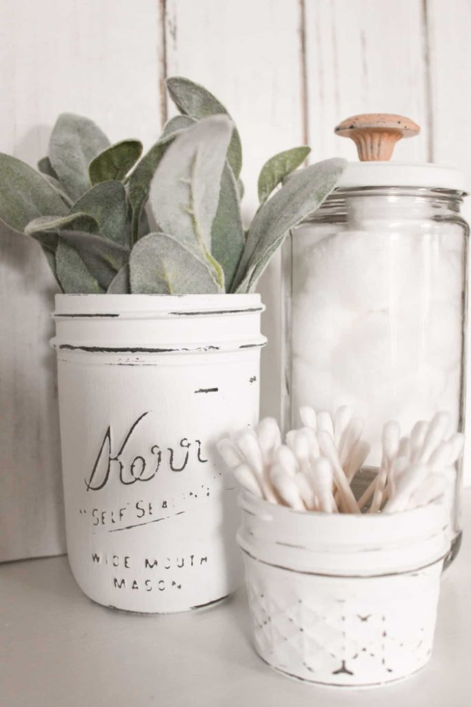 Three white farmhouse style upcycled jars for bathroom decor.  Each jar is a different size and holds qtips, a plant and cotton balls