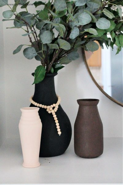 Three different DIY faux ceramic vases on a mantel. One vase is black, one is brown, and one is cream coloured. The black vase is the largest with a wooden farmhouse string of beads and has branches of greenery. They are all sitting beside a round mirror with metal frame.
