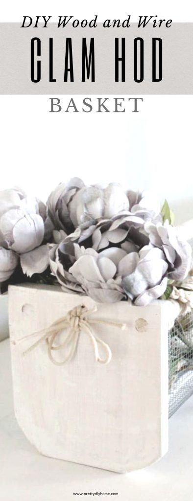 A diy clam hod basket painted white for fall decor. It has greyish flowers and white birch logs in it. They can also be used for eggs, or washing vegetables outdoors while gardening, but this one is indoors on a fireplace mantel for Fall decorating.