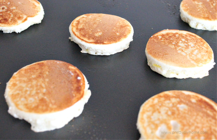 Mini golden brown lemon ricotta pancakes being cooked on a grill.