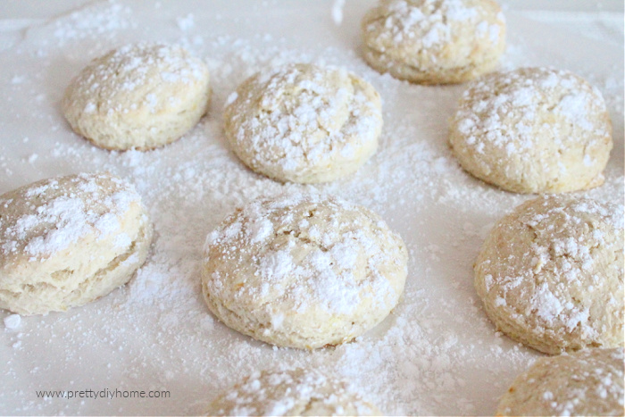 A baking tray full of light golden biscuits that are covered with a dusting of icing sugar.
