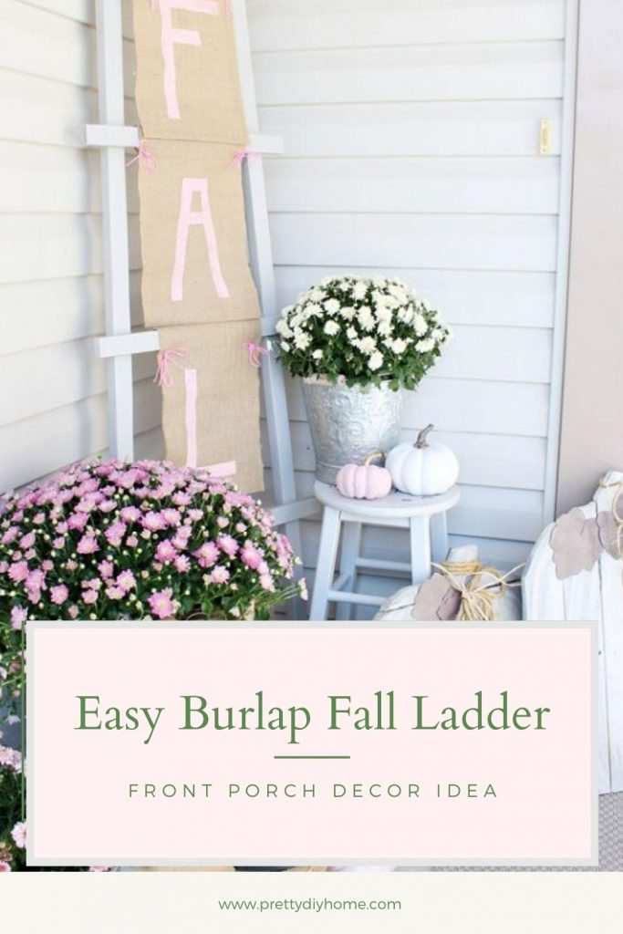 Fall front porch ideas in pinks and creams with pink mums with beautiful burlap bows, painted pink pumpkins and white wood stools. The background is a farmhouse ladder with a large Fall burlap banner with pink letters that say FALL.
